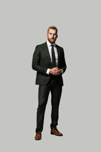 Serious Looking Handsome Caucasian Businessman Looking Serious With A Beard And Wearing A Suit And Tie, Hands Clasped On A Grey Background.