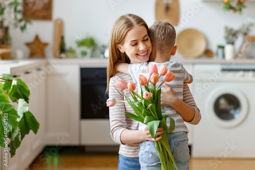 Grateful mother with bouquet hugging son #414547583
