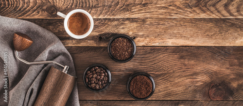 Tableau sur Toile Manual Coffee grinder and jars of fresh ground coffee from roasted beans on wooden rustic table