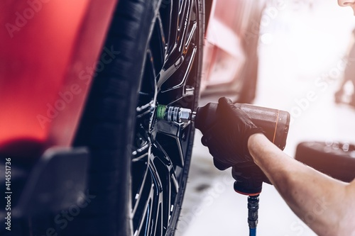 Fototapeta Changing car tire and wheel in the professional car mechanical service obraz