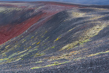 Iceland, Southern Highlands, Fjallabak Region The Black Lava Surrounding A Crater Is Punctuated With Bits Of Red Mineral Outcrops And Some Bright Green Moss.