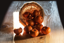 Page Mandarins Or Tangerines Spilling From A Basket On Woden Table, Backlit By Morning Sun