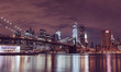Illuminated Brooklyn Bridge And Buildings By River Against Sky At Night in New York City
