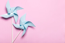 Blue Paper Spinners On Light Pink Background. Kids Toys Colorful Pinwheels On Celebration Party Background. Top View, Flat Lay