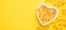 Omega 3 Capsules In A Heart-shaped Plate On Yellow Background. Fish Oil Softgels. Supplement Food Vitamin D Capsules. Copy Space - Image