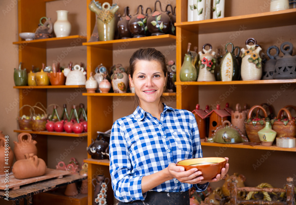Fototapeta Portrait of young woman demonstrating finished production in pottery workshop