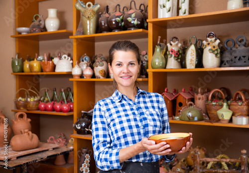Fototapeta Portrait of young woman demonstrating finished production in pottery workshop obraz