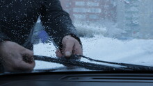 A Look Through The Windshield Of A Car At The Hands Of A Driver Who Removes Snow From The Car Wipers During A Heavy Snowfall With A Downpour, Cleaning And Checking The Work Of The Car Wipers