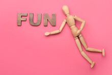 Wooden Mannequin With Word FUN On Color Background