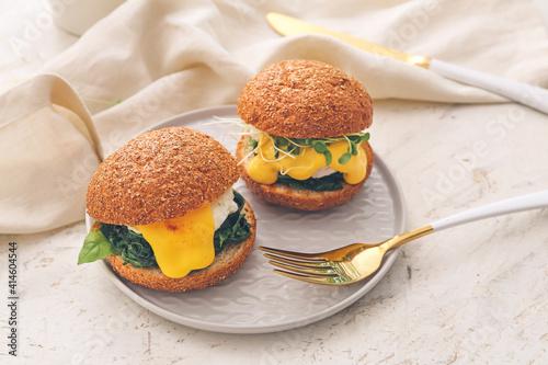 Fotografiet Tasty burgers with florentine eggs on light background