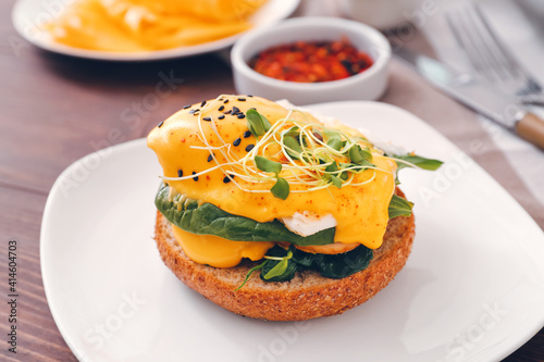 Fototapeta Tasty sandwich with florentine egg on wooden background, closeup