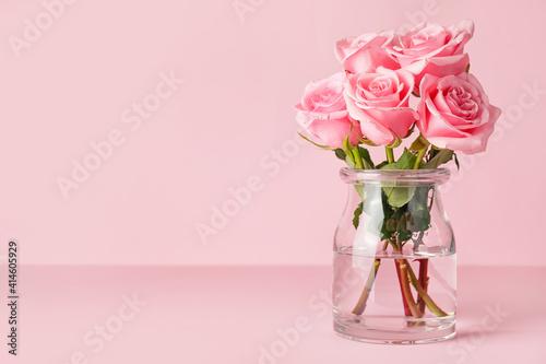 Beautiful pink roses in vase on color background © Pixel-Shot
