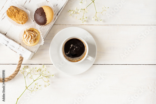 Top view of cup of black coffee and mini cakes on a wooden tray with copy space. Morning breakfast composition © IKvyatkovskaya