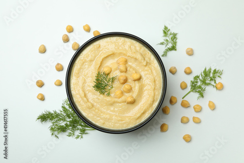 Fototapeta Bowl of hummus and dill on white textured background