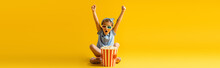 Excited Kid In 3d Glasses Sitting With Crossed Legs And Raised Hands Near Popcorn Bucket And Watching Movie On Yellow, Banner