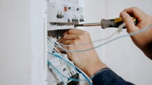 An Electrician Assembles An Electrical Panel In An Apartment. Electrical Box Contains Many Terminals, Relays, Wires And Switches. Manufacture And Installation Concept Concept.