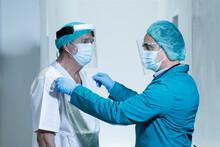 Coppia Di Medici Si Aiutano Nella Preparazione Con Tutte Le Protezioni Prima Di Un Intervento Chirurgico In Ospedale