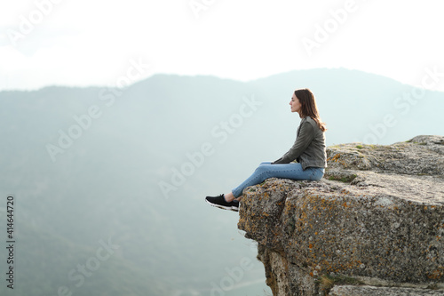 Tablou Canvas Woman contemplating views on the top of a cliff in the mountain