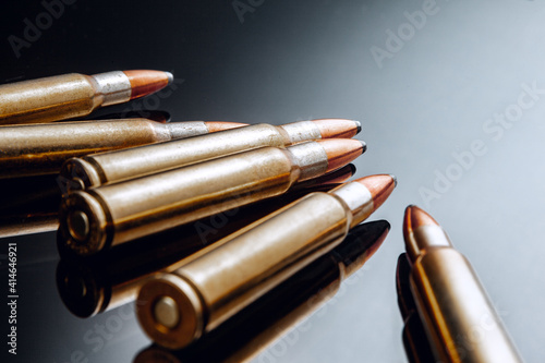 Rifle bullets or cartridges on black shiny background Fototapet