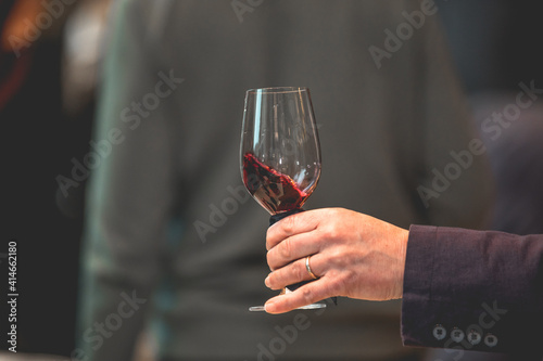 Tablou Canvas Close up on a hand holding a glass of red wine