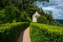 Ermita Rodeada De Vegetación Al Final De Un Camino Formado Por Setos De Jardín