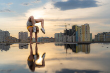 Flexible Female Gymnast Doing Handstand And Calisthenic With Reflection In The Water On Cityscape Background During Dramatic Sunset