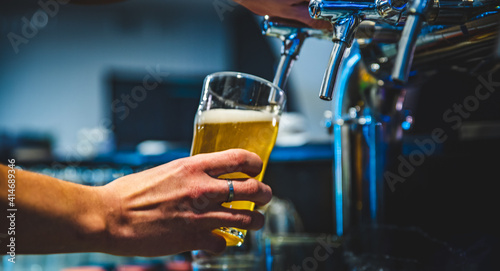 Fotografie, Obraz bartender hand at beer tap pouring a draught beer in glass serving in a restaura