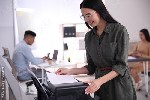 Employee using new modern printer in office © New Africa