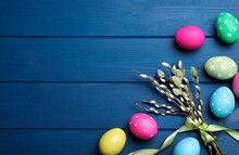 Bright Painted Eggs And Pussy Willows On Blue Wooden Table, Flat Lay With Space For Text. Happy Easter