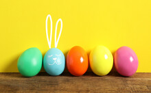 Blue Egg With Drawn Face And Ears As Easter Bunny Among Others On Wooden Table Against Yellow Background
