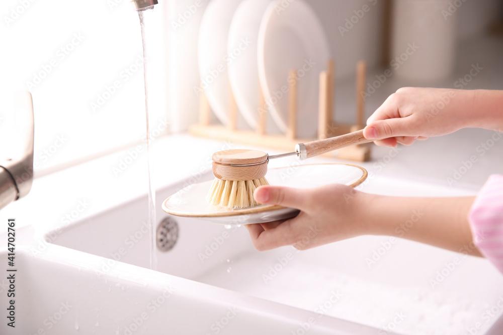 Fototapeta Little girl washing dishes in kitchen, closeup