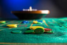 Roulette In Legno Isolata Sopra Un Tavolo Da Gioco Verde Con Fiches Colorate