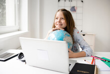 Beautiful, Young, Blond Girl Is Sitting In Front Of Laptop Holding Globe In Her Hands And Dreaming About Vacation And End Of Pandemic And Covid 19