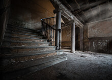Dark Creepy Old Basement With Stone Staircase Leading To Cellar Underground Light Rays Shining To Make Shadows On Old Stone Tiled Floor  And Pillars Supporting Decaying Old Derelict Ceiling