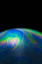 Rainbow Soap Bubble On A Black Background. Close-up Of A Colorful Surface.