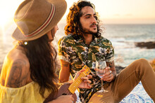 Young Fashionable Hippie Couple On A Romantic Picnic On The Beach, Playing On Ukulele Guitar And Singing Songs. Sunset Light. Summer Time.