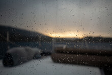 Closeup Shot Of Raindrops On A Ship Window With A Beautiful Sunset In The Background