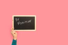 Mano De Mujer Sosteniendo Una Pizarra Con La Palabra Be Positive Sobre Un Fondo Rosa Liso Y Aislado. Vista De Frente. Copy Space