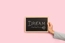 Mano De Mujer Sosteniendo Una Pizarra Con La Palabra Dream Sobre Un Fondo Rosa Liso Y Aislado. Vista De Frente. Copy Space