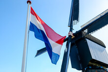 The Dutch Flag Waving In Front Of A Traditional Windmill In Kinderdijk In The Netherlands