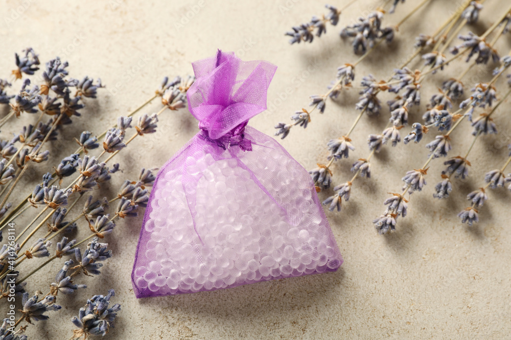 Fototapeta Scented sachet with aroma beads and dried lavender on grey table, flat lay
