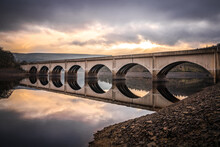 Long Arched Bridge Crossing Ladybower Reservoir Reflected In Derwent Valley Still Deep River Water With Sunrise Beautiful Orange Sky Setting Behind In The Peak District Landscape