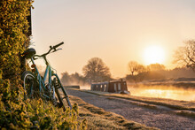 Canal Boat With Mountain Bike Left Leaning Against Hedge Row Early Morning Sunrise Dawn With Golden Light In Sky On The River Trent And Mist Rising In Nottingham Biker On Ride Out