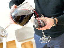Man Wearing Black Golf Pouring Red Wine In A Glass.