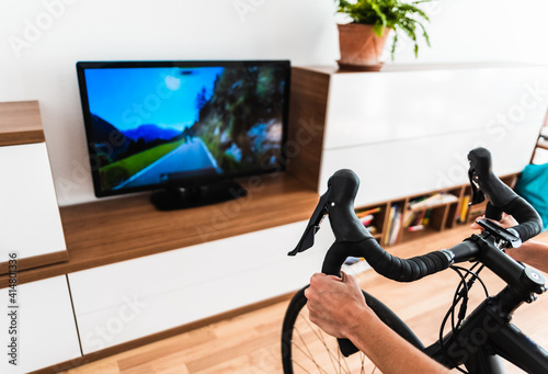 Obraz Cycling Indoor with exercise bike trainer motivating himself with the gamification of sport. - fototapety do salonu