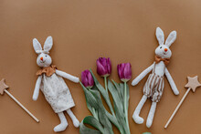 Two Rabbits, Rainbow And Tulips On Brown Background. Top View, Flat Lay
