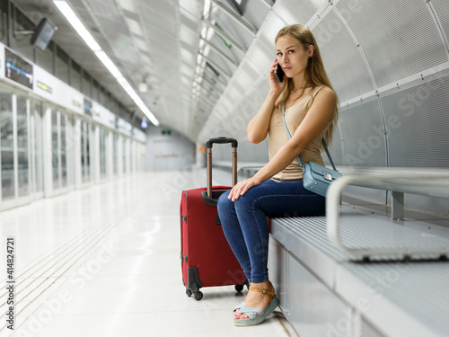 Fototapeta Portrait of young female tourist sitting on bench and using phone while waiting subway car obraz