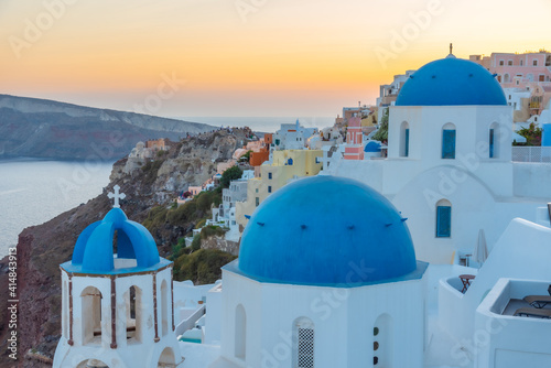 Canvas Print Sunset view of churches and blue cupolas of Oia town at Santorini, Greece