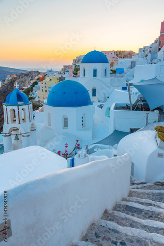 Obraz na plátne Sunset view of churches and blue cupolas of Oia town at Santorini, Greece