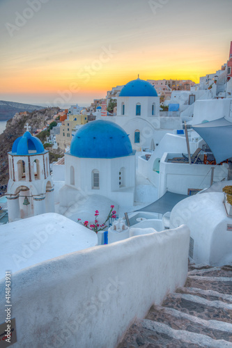 Photo Sunset view of churches and blue cupolas of Oia town at Santorini, Greece